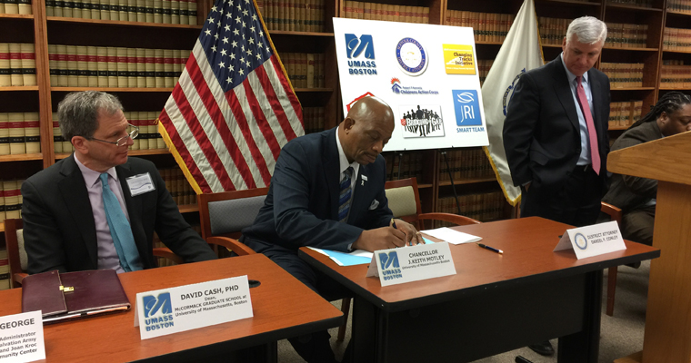 Chancellor J. Keith Motley signs the MOU while Dean David W. Cash (left) and DA Dan Conley (right) look on.