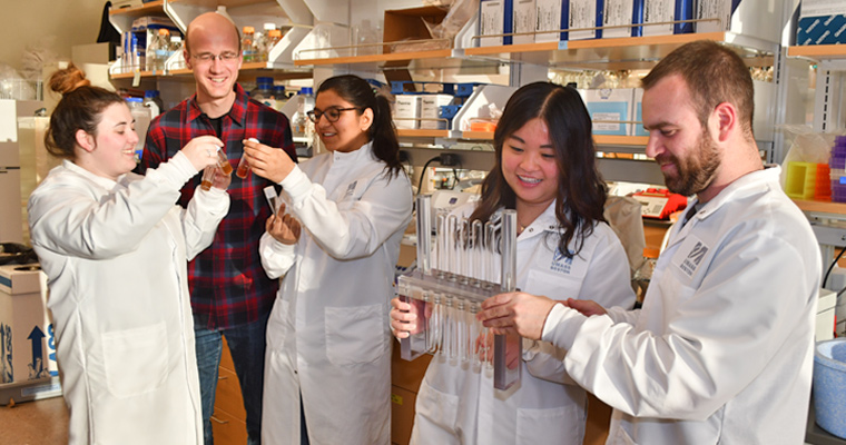 Jens Rister and four graduate students in his lab, holding up vials