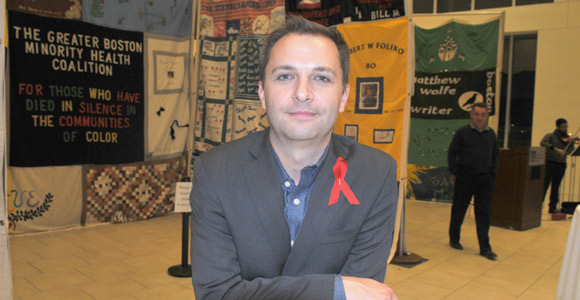 AIDS Action Committee Executive Director Carl Sciortino in front of the AIDS Memorial Quilt