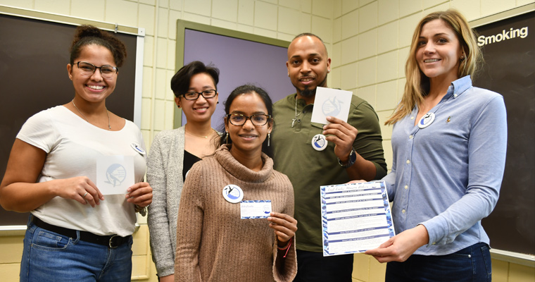 Taelise Ricketts, Samatha Pham, Laxmi Spearing, Estanislau Ribeiro, and Molly Brady show off stickers, buttons, business cards, and fact sheets encouraging people to protect the oceans by limiting plastic use