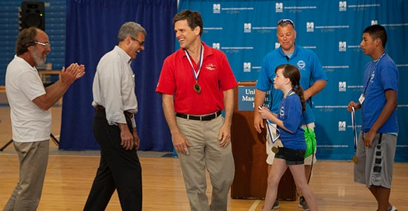 Gary Siperstein (far left), Tim Shriver (middle), and Camp Shriver campers receive medals.