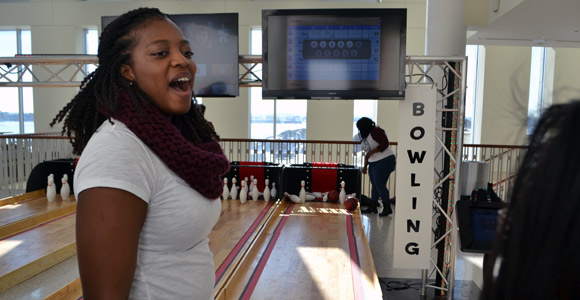 Raenelle Teesdale celebrates her bowling score in UMass Boston's Campus Center.