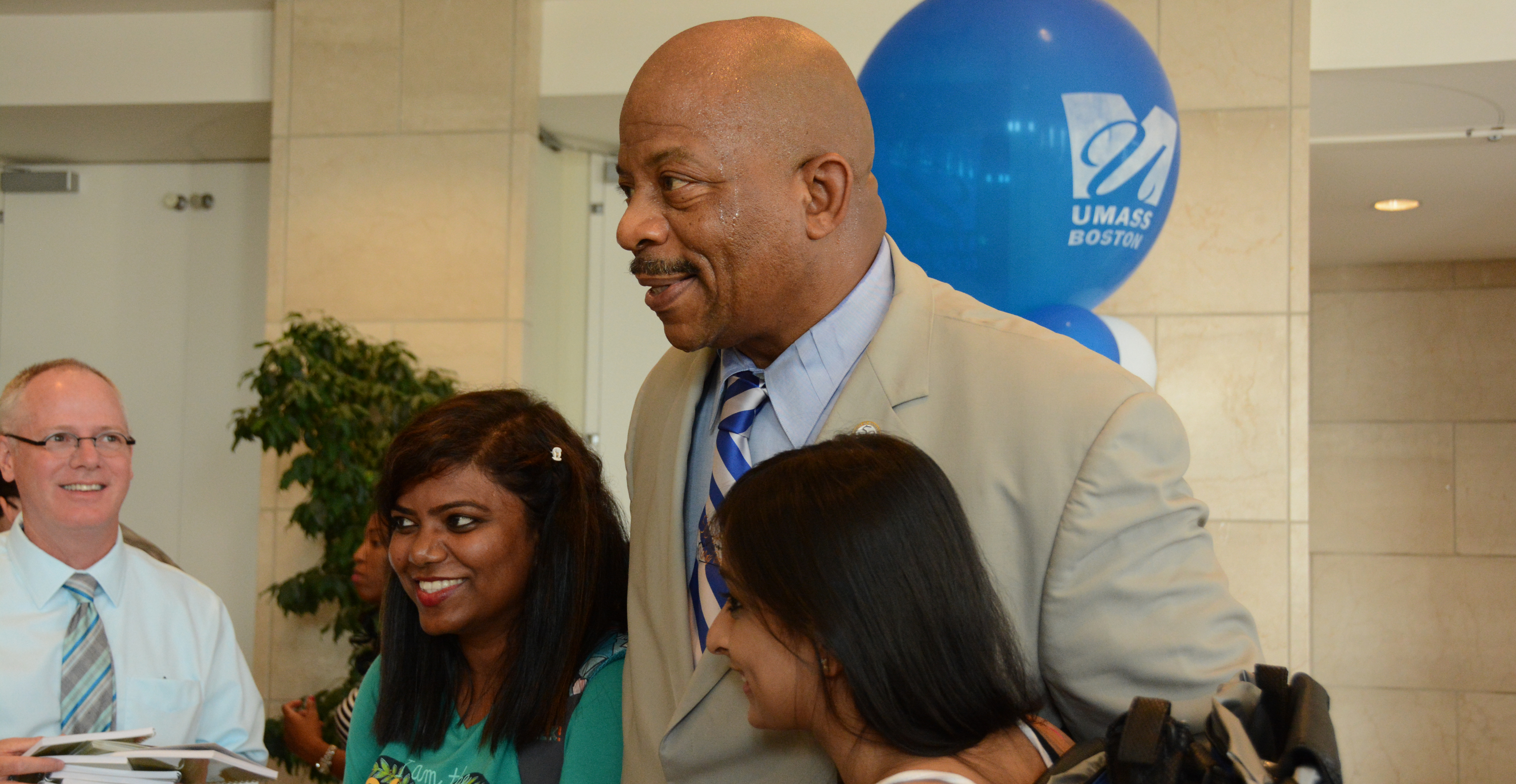 Chancellor J. Keith Motley poses for a selfie with two students.