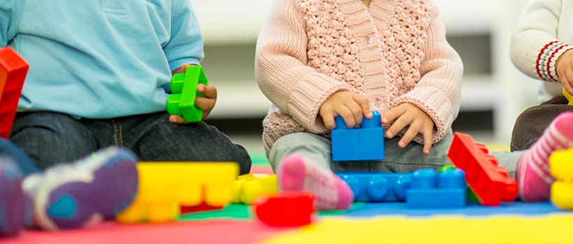 Closeup of toddler hands on building blocks