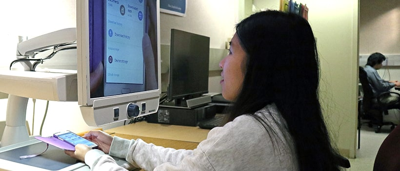 Student at UMass Boston looking up at computer screen using assistive technology to view her mobile phone