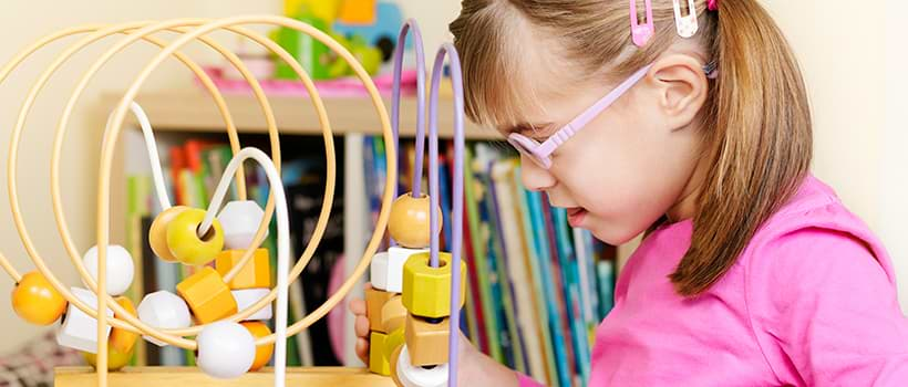 Young girl with visual impairment wearing glasses and playing with tactile toy