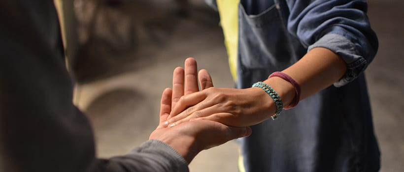 closeup of hands outstretched and one supporting the other