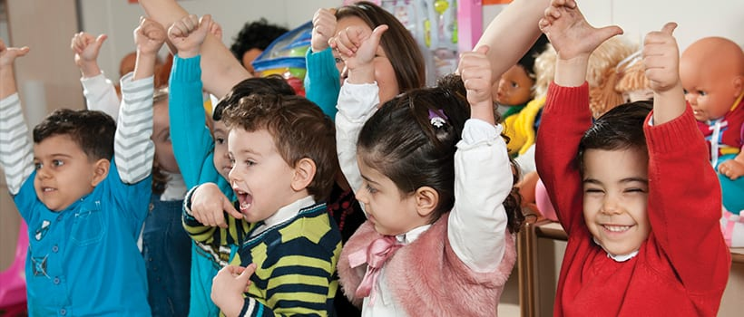Laughing toddlers reaching for the sky