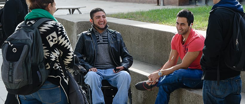 Student in wheelchair talking to other students on the UMass Boston campus