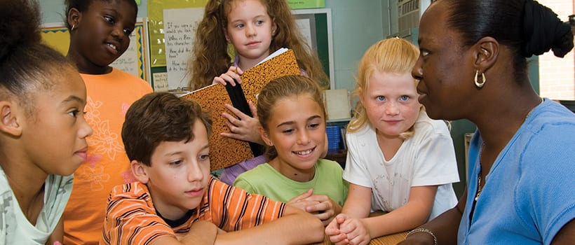 Elementary students surround an adult in a classroom setting