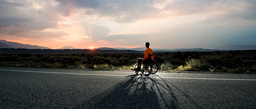 person in a wheelchair on the road gazing off at sunrise, mountains.