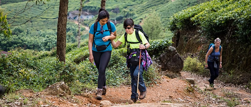 Sighted female hiker leading a blind hiker up a trail in a tropical forest.