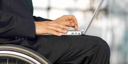 Image of a man wearing a suit, sitting in a wheelchair, and using a laptop computer.