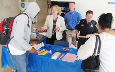 Students approach an information table about emergency preparedness