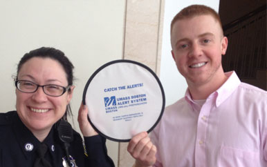 Diane Kirkpatrick and Justin Comeau hold up a frisbee that says Catch the Alerts! UMass Boston Alert System