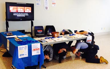 Participants in a Great Shakeout Earthquake Drill demonstrate what to do, ducking for cover under a table.
