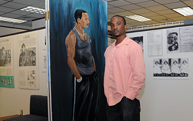 Student standing with a painting.