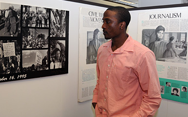 Student stands next to posters in the Trotter Institute