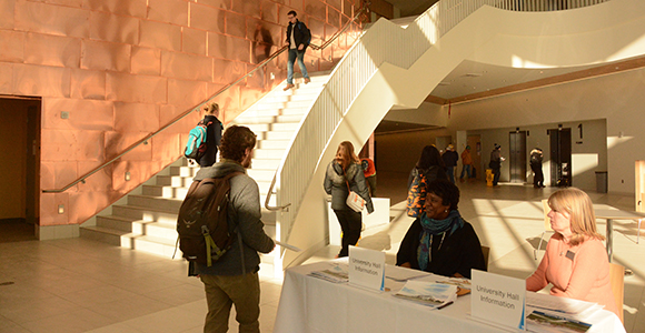 Students enter University Hall and are greeted by two UMass Boston staff members.
