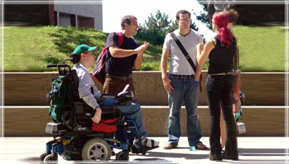 Person in a wheelchair in a group of people talking
