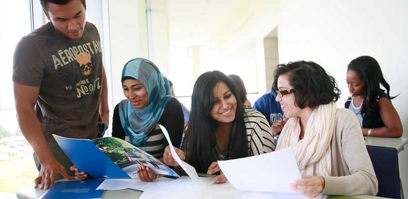 Students reading UMass Boston brochures