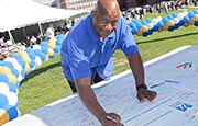 Chancellor J. Keith Motley celebrated UMass Boston's 50th anniversary at the UMass Boston Birthday Block Party on June 18, 1964 by signing a giant birthday card.