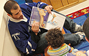 UMass Boston hockey captain Jimmy Ennis reads to children at UMass Boston's Early Learning Center.