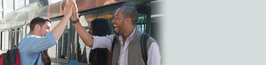 Two UMass Boston students exchange a high five outside one of the shuttle buses