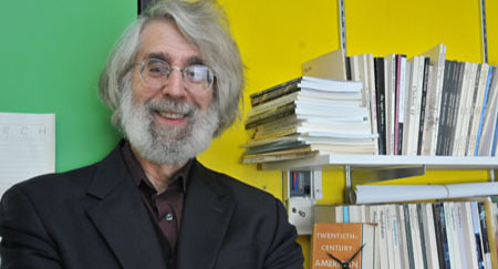 Lloyd Schwartz poses for a picture, surrounded by books.