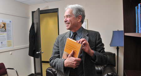 Professor and author Ed Tronick with his book.