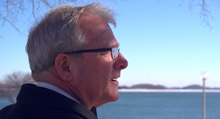 Bill Walczak '79 looks out over the water on UMass Boston's Columbia Point campus.
