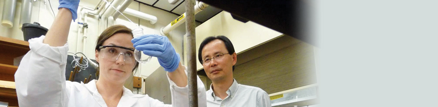 Wei Zhang, Professor of Chemistry and Director of the Center for Green Chemistry, works with student in lab.