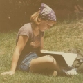 A student reads on the green on the Columbia Point campus.